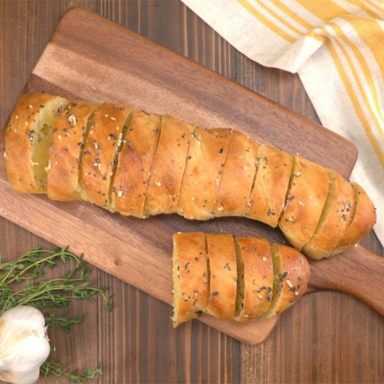 Overhead hasselback garlic cheesy bread on wood cutting board