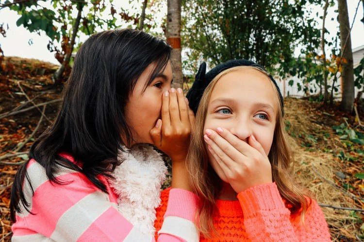 Image of girls whispering.