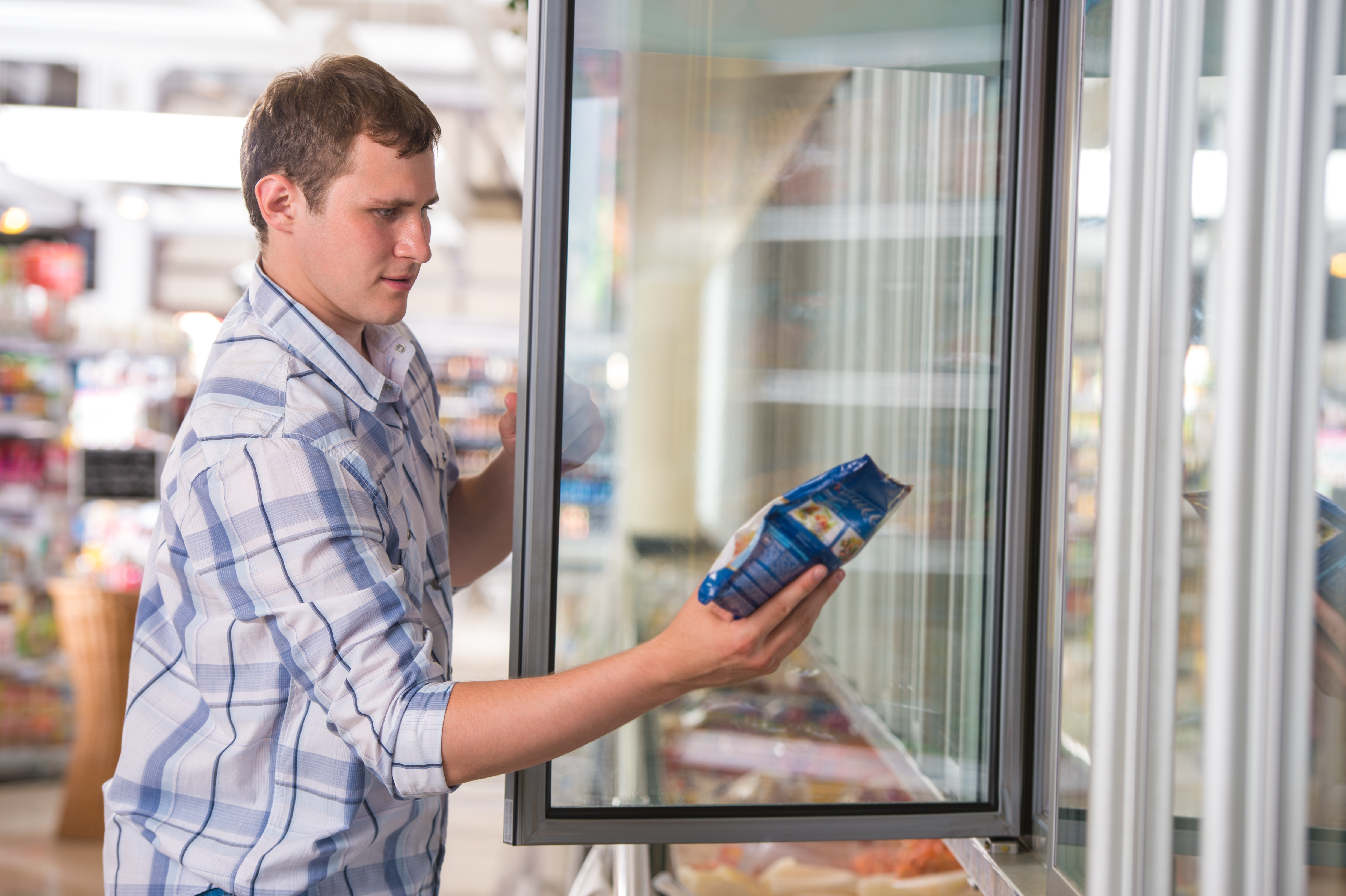 Man in a supermarket standing in front of the freezer