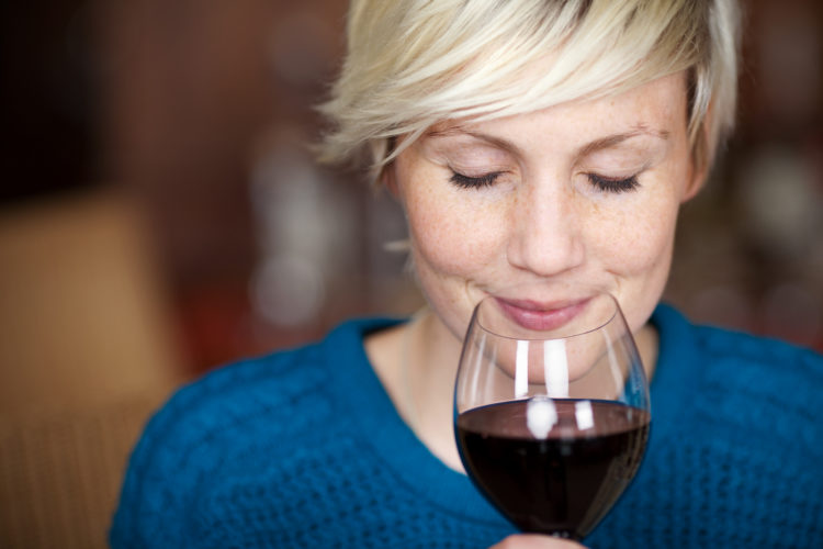 Image of closeup portrait of young female customer drinking red wine with eyes closed