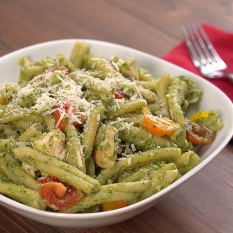 Bowl of avocado pesto chicken pasta topped with Parmesan