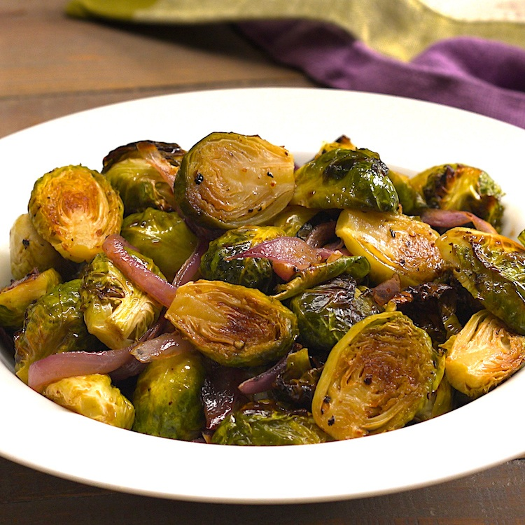 Roasted Brussels sprouts caramelized in the oven then glazed with a bright balsamic & honey dressing for a colorful veggie side dish that bursts with flavor.