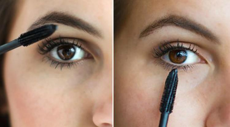 Holding a mascara wand vertically.