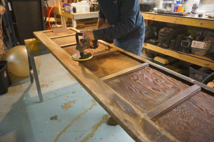 man sanding garage door table