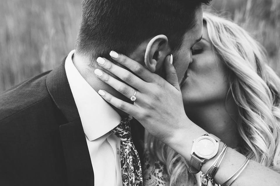 Couple kissing after engagement.
