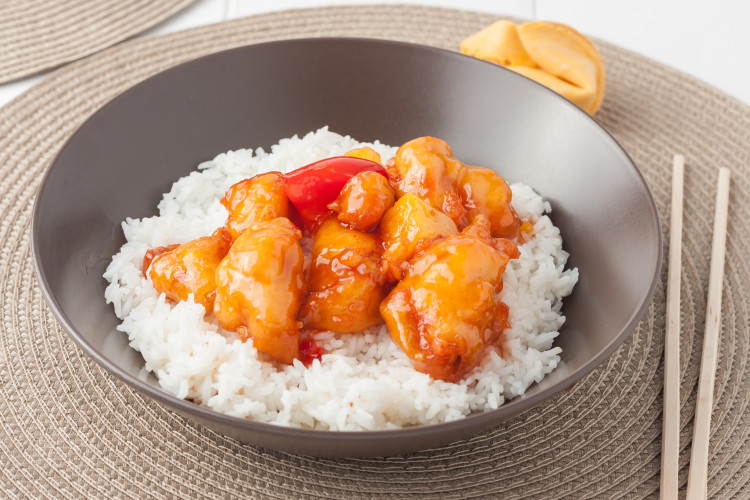 Sweet and sour chicken with rice in brown bowl