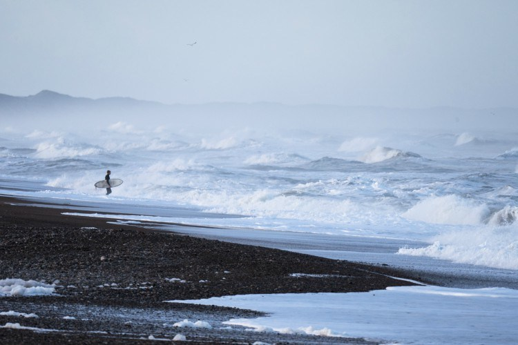 surfer stands by large waves