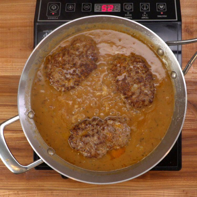 Salisbury Steak cooking in pan with gravy