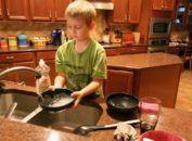 Boy washing dishes.