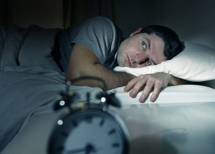 Image of young man in bed with eyes opened suffering insomnia and sleep disorder thinking about his problem