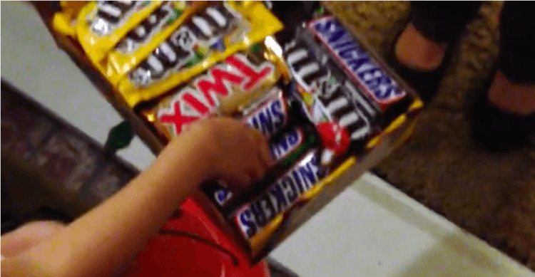 girl grabs a Snickers bar