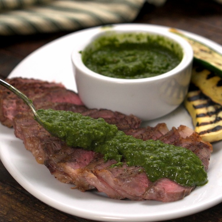 Spreading chimichurri sauce on steak