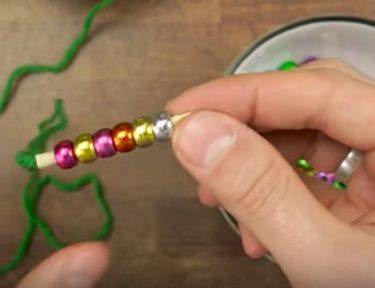 person beading a piece of yarn