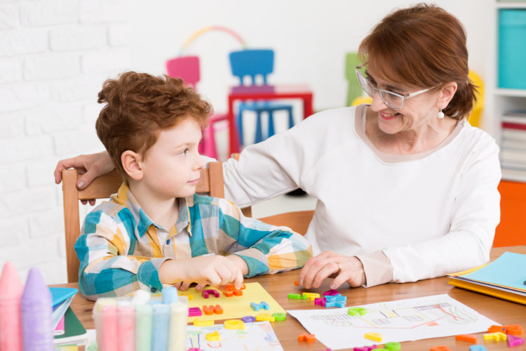 Image of woman therapist sitting at a desk, close to the young boy