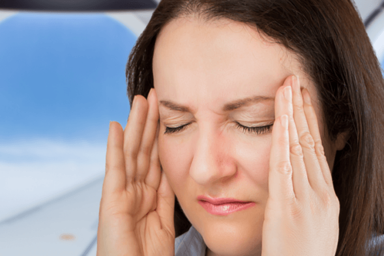 woman with a headache on an airplane