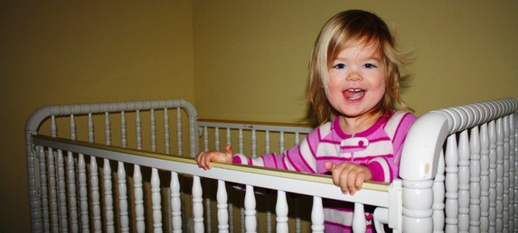 happy baby standing in crib