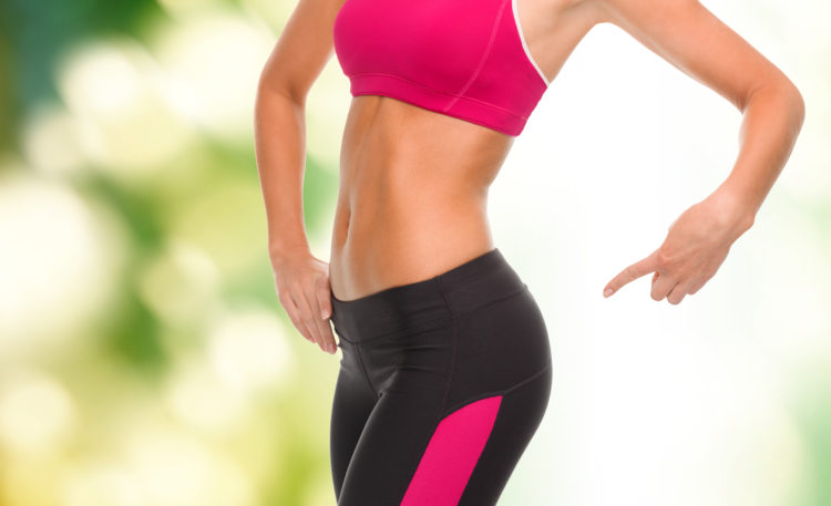 Image of fitness and diet concept - close up of sporty woman pointing at her buttocks