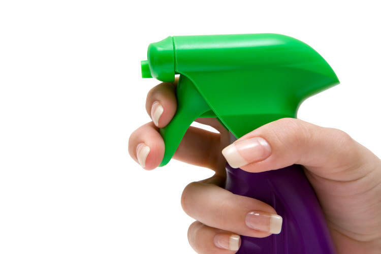 Woman using a spray bottle. Isolated on a white background.