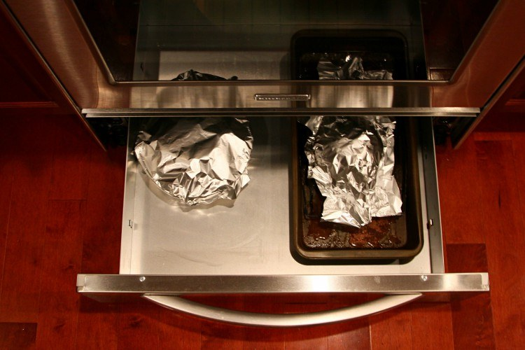 open warming drawer with food items inside