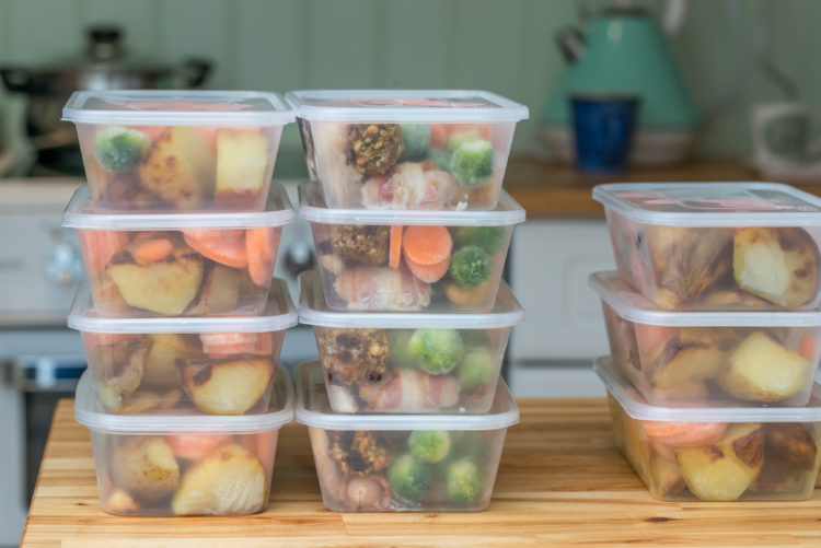 Image of stack of home cooked roast chicken dinners in containers ready to be frozen for later use as quick and easy ready meals.