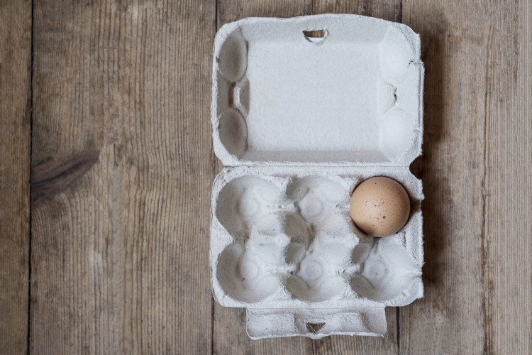 One egg in a carton on an old wooden table
