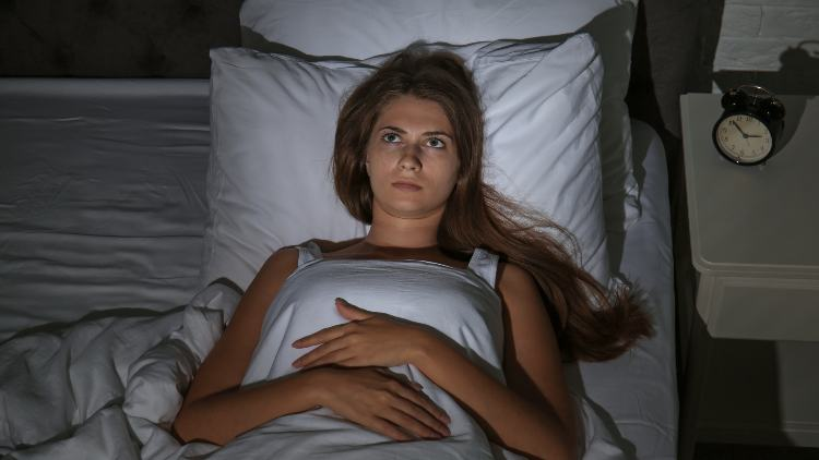 Image of woman awake in bed