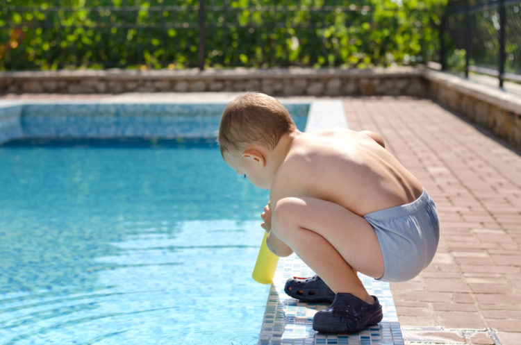 Image of young boy playing at the edge of a swimming pool