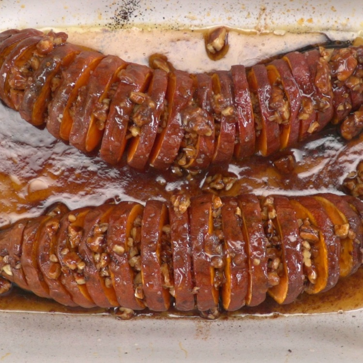 Hasselback-cut sweet potatoes filled with maple pecan glaze in pan
