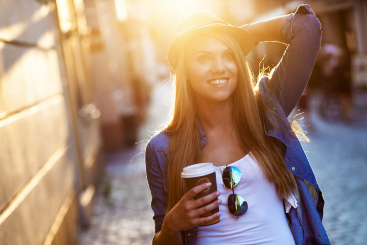 Image of young stylish woman drinking coffee to go in a city street