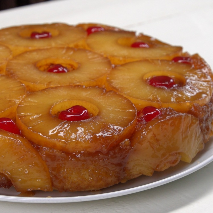 Baked pineapple upside-down cake on white plate