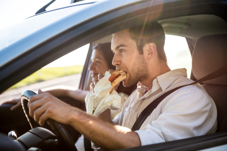 Image of man eating while driving