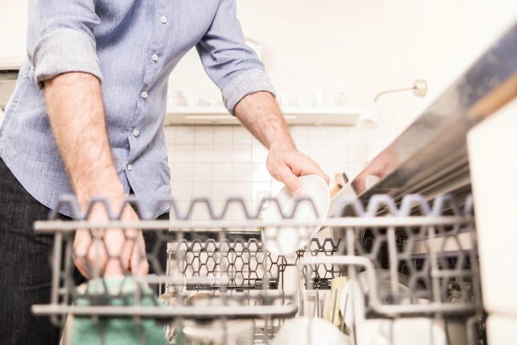 Image of man loading dishwasher.
