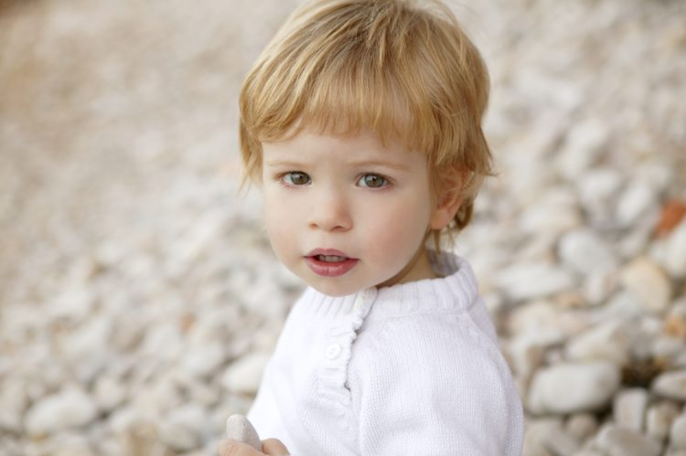 Image of beautiful blond boy portrait winter outdoor, stones background