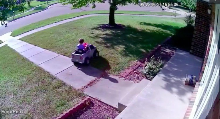 boy drives toy car on lawn