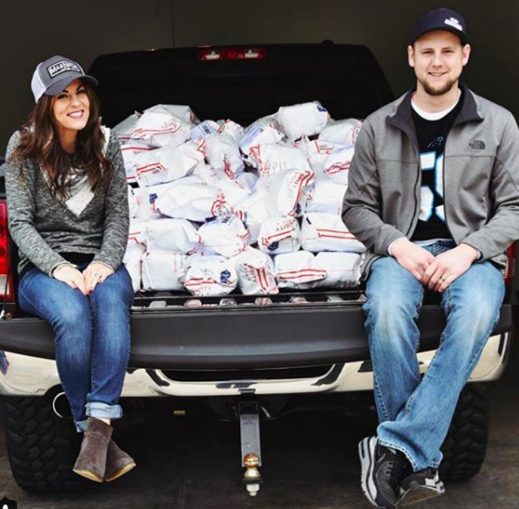 Image of Kenzi and Austin Reddick with mugs in a truck.