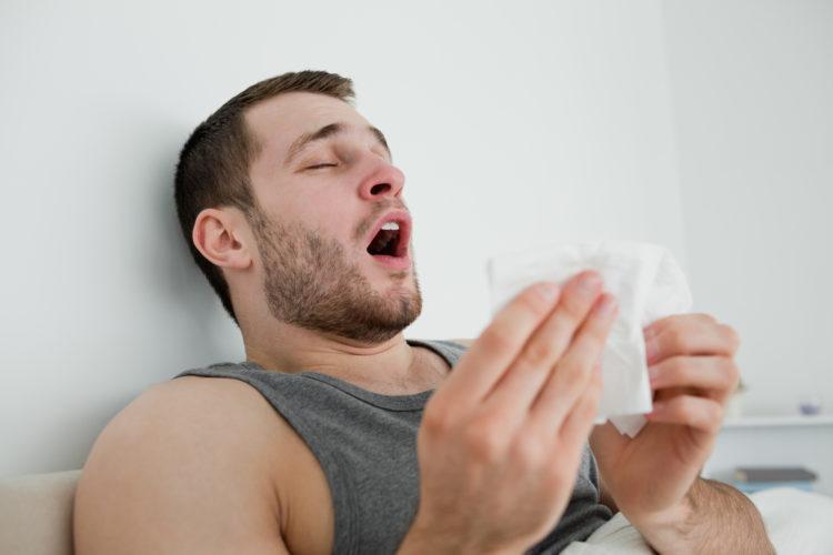 Image of man sneezing
