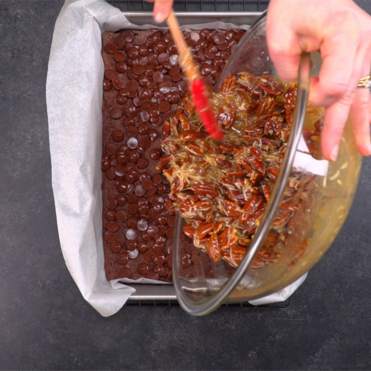 Pouring pecan topping on German chocolate crust base