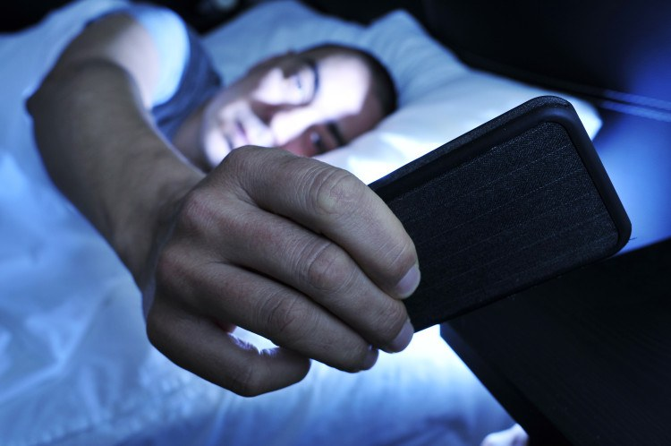 young man looking at the smartphone in bed at night