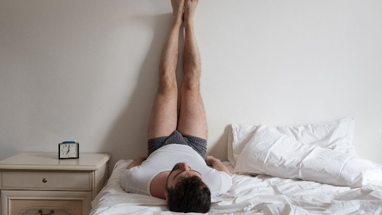 Man stretches muscles on the bed in the bedroom in the morning