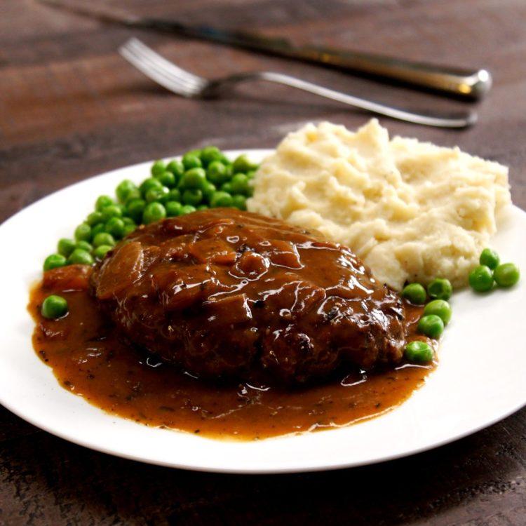 Salisbury Steak brown onion gravy peas mashed potatoes plate