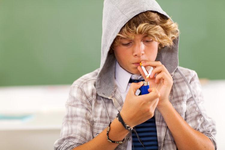 Image of teen boy lighting a cigarette