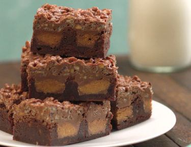 Fudgy brownies topped with a crackly layer of crispy rice cereal coated in melted chocolate and crunchy peanut butter--with a surprise peanut butter cup center.