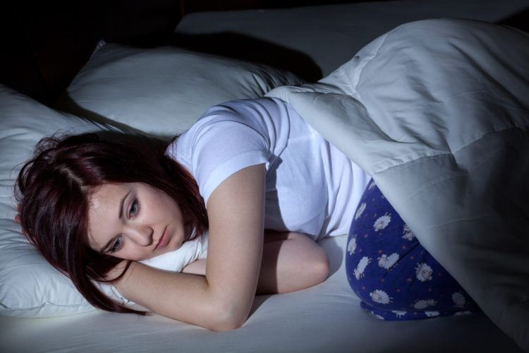 Woman stays up in bed unable to sleep.