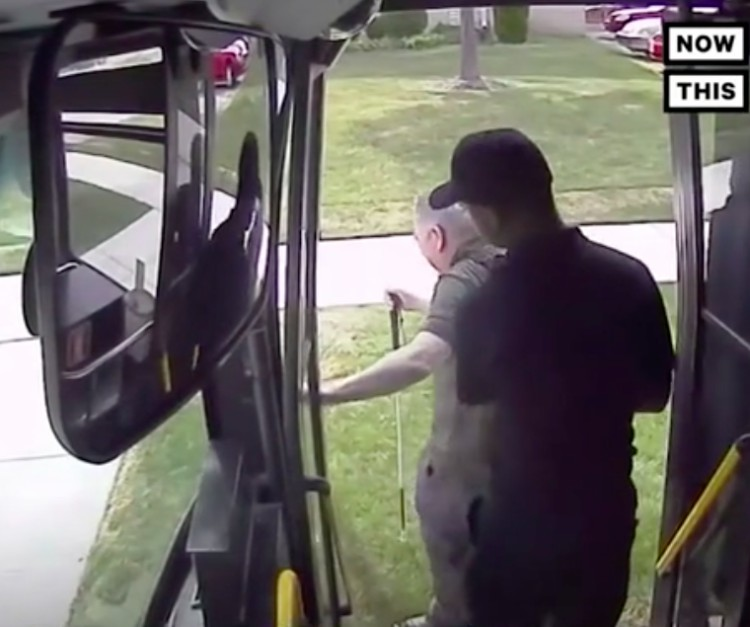 Image of man helping blind man off his bus