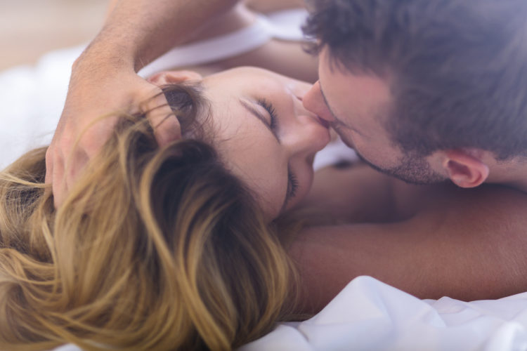 Image of couple kissing in bed