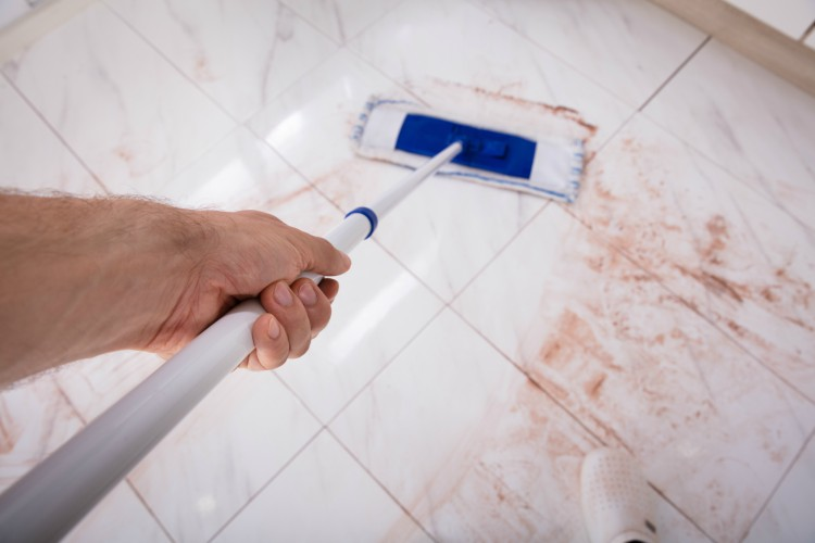 Image of man cleaning kitchen floor.
