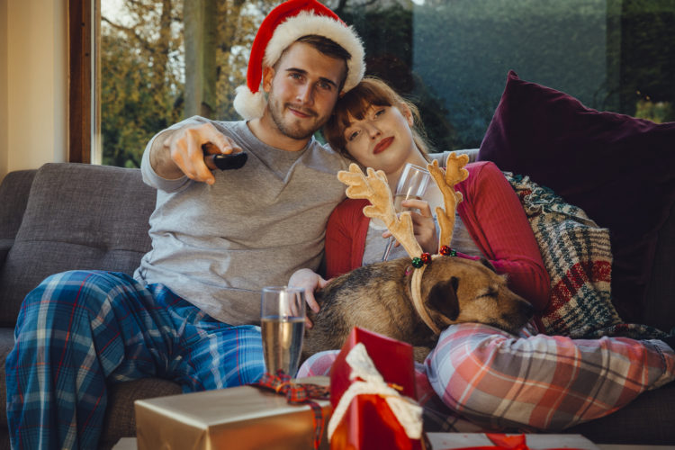 Image of young couple at home with their pet dog at Christmas time. They are all cuddled up on the sofa at home, watching television.