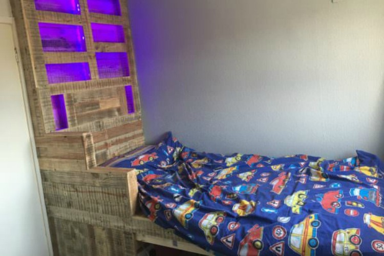 Raised kid's bed with over-sized LED headboard