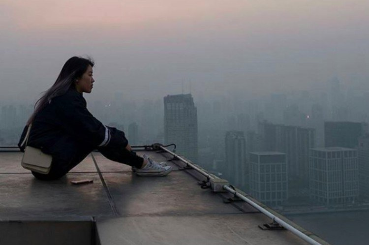 woman looks at pollution from rooftop