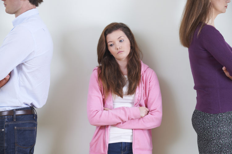 Image of Teenage Girl Standing Between Parents Not Speaking To Each Other